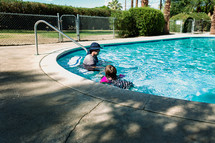 a father and daughter swimming in a pool