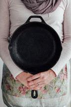 a woman holding up a cast iron skillet
