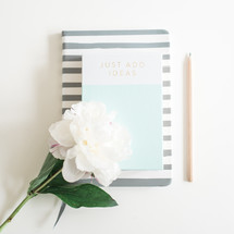 pencil, book, journal and flowers on a white desk