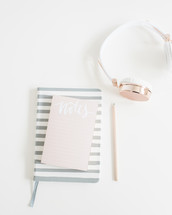 notepad, journal, pencil, and headphones on a desk