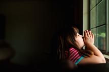 a girl praying in a window