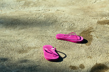 pink flip flops on concrete