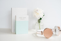 flowers in a vase, book, journal and headphones on a white desk