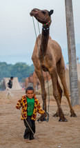 a child leading a camel in India