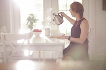 a woman sitting at a kitchen table reading a Bible