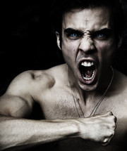 Adam Virtue; man yelling with piercing, brilliant blue eyes and cross on forehead.