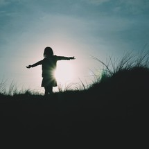 silhouette of a girl with outstretched arms at sunset