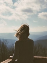 a woman looking over a railing at mountains