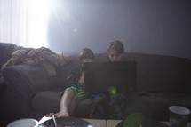 brothers sitting on a couch looking at a computer