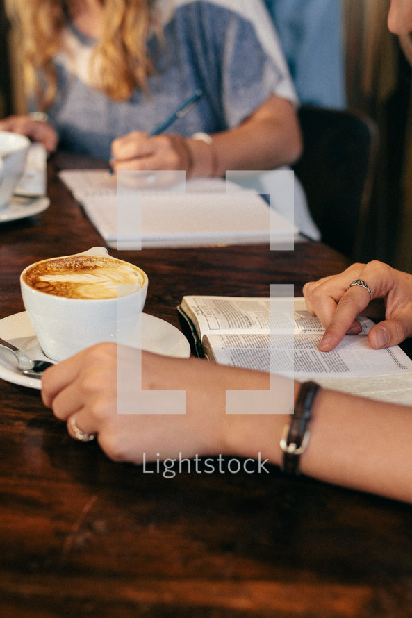 a woman writing in a notebook in a coffee shop at a Bible study