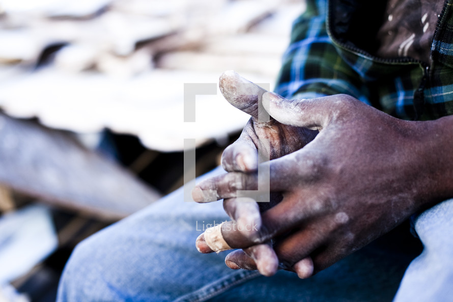 man with his fingers laced in prayer