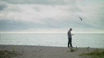 a man walking on a beach reading a Bible
