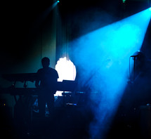 man on stage standing under a blue spot light