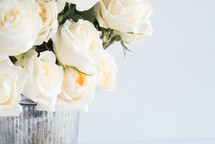 white roses in a metal bucket