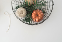 metal basket with pumpkins and twine