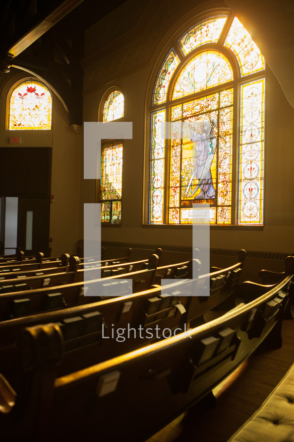 Sunshine through a decorative stained glass window in a church sanctuary.