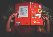 a child reading a Dr Seuss book