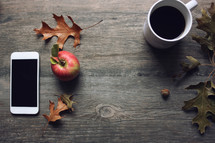 coffee cup, fall leaves, and apple on wood background