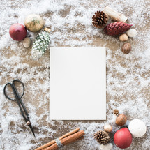white paper in snow with border of scissors, cinnamon sticks, and pine cones