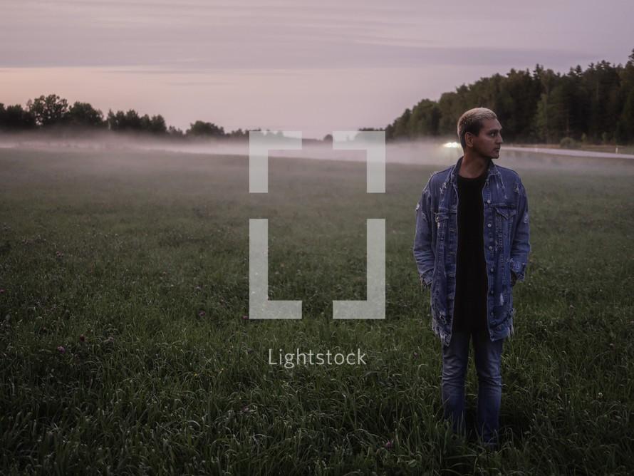 a man standing in a foggy field in Sweden