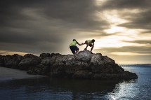 brothers helping each other up rocks along a shore