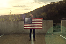 a man holding the edge of an American flag