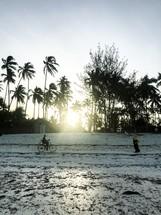 man riding a bike on a beach in Zanzibar, Tanzania
