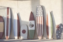 boogie boards and surfboards with flags from various nations painting on them