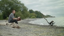 man sitting on a beach reading a Bible and praying