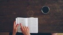 Woman's hands turning the pages of an open Bible on wooden table with a cup of coffee.