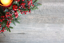 red berries and Christmas greenery on a wood background