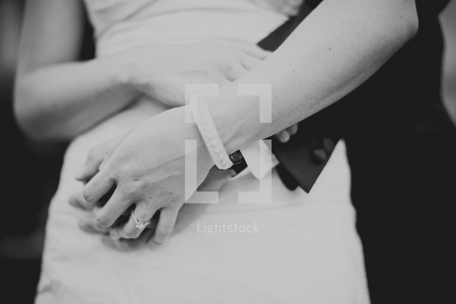 A bride and groom hold hands while hugging one another.