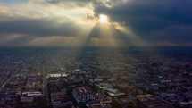 God rays (crepuscular rays) shining on a city in an aerial timelapse.