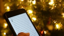reading a Bible verse off a phone in front of a Christmas tree