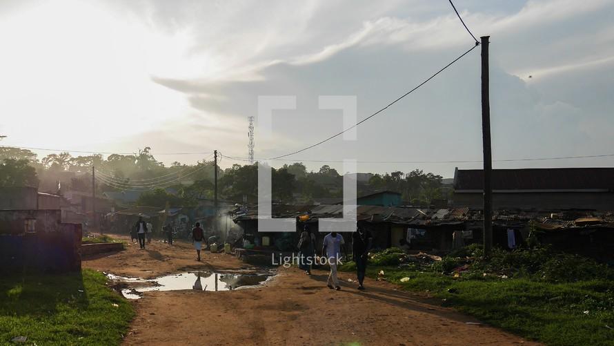 people walking on a dirt road in Uganda