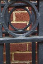 Brick wall through an iron gate.