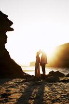 couple kissing under a sunburst on the beach