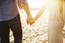 couple holding hands walking on a beach
