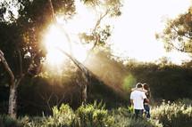 sunburst through the trees shining over a couple hugging