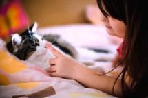 a little girl petting a cat