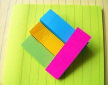 Various colors and types of paper with layers of colored sticky note paper raised above the surface to create a 3D effect with various colored sticky notes and paper.