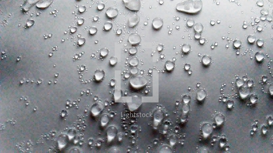 Small and large beads of water droplets and condensation begin to appear on a flat surface when cold weather and warm air mix and ice begins to melt forming condensation and life from water.