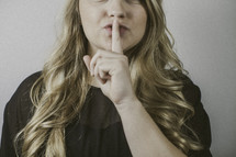 woman holding a finger in front of her mouth