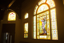 Sunshine through decorative stained glass windows.
