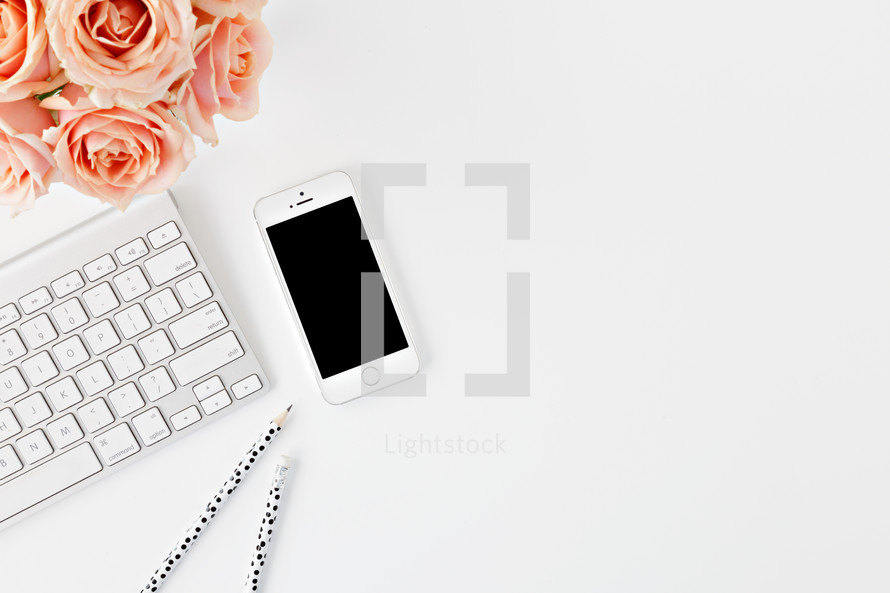 phone, computer keyboard, pencils, and peach roses on a desk