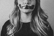 woman with tape over her mouth