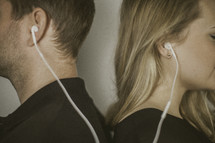 couple standing back to back listening to earbuds