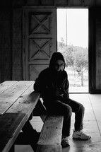 a boy sitting at a picnic table in a barn