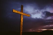 Wooden cross outside at nightfall.