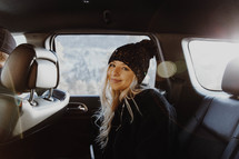 a young woman sitting in the backseat of a car
